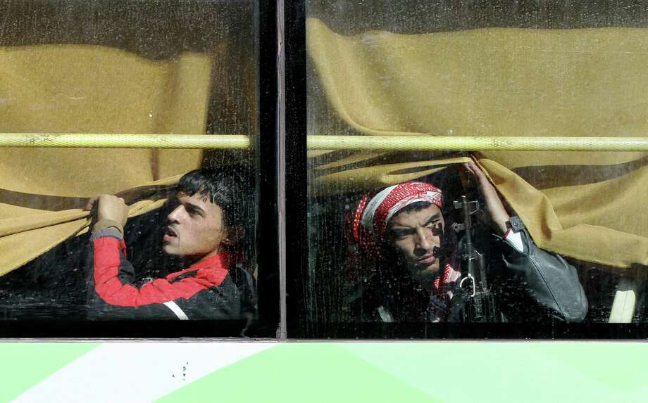 Syrian rebel fighters are seen on a bus as hundreds of civilians and rebel forces began evacuating the last opposition-held district of Waer in the central city of Homs under a deal with the Syrian government. Photo: Louai Beshara /Getty Images / AFP