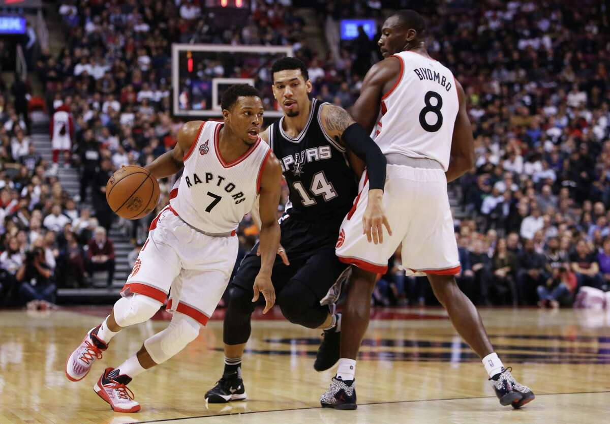 TORONTO, ON - DECEMBER 09: Kyle Lowry #7 of the Toronto Raptors dribbles the ball as Danny Green #14 of the San Antonio Spurs defends during an NBA game at the Air Canada Centre on December 09, 2015 in Toronto, Ontario, Canada. NOTE TO USER: User expressly acknowledges and agrees that, by downloading and or using this photograph, User is consenting to the terms and conditions of the Getty Images License Agreement.