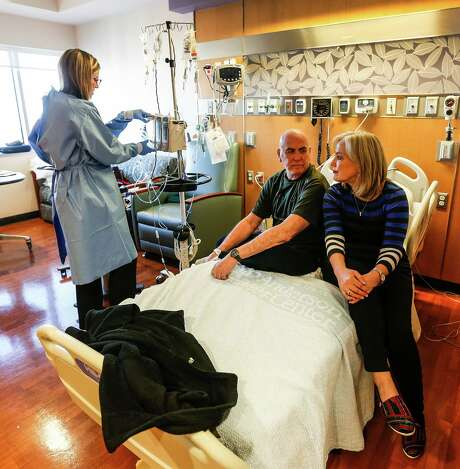 Barbara Holt comforts husband Duane Rossmann while he receives chemotherapy for lymphoma on Wednesday at MD Anderson. Rossmann is about to lose his PPO, which will force him to change hospitals.  Photo: Karen Warren, Staff / © 2015  Houston Chronicle