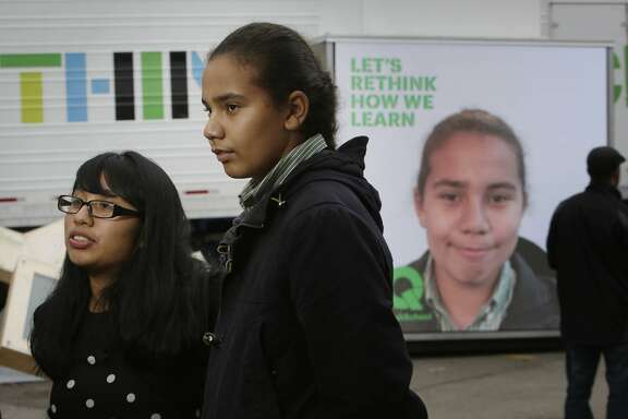 Maya Martin (l to r), 16, junior West High School, Aaron Jackson, 15, sophomore West High School stand together as they are interviewed for a promotional video at the XQ roadshow while Jackson's image is displayed on the XQ We Think booth behind her on Wednesday, December 9,  2015 in Oakland, Calif.
