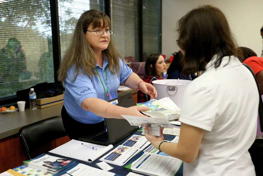 Majorie Monson hands out information about the Affordable Care Act federal marketplace insurance benefits at a Houston event last month. By week five of open enrollment, 317,094 people in the state had chosen plans on the exchange. Photo: Gary Coronado /Houston Chronicle / © 2015 Houston Chronicle