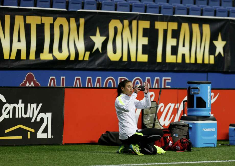 Goalie Hope Solo checks out her photo before practice at the Alamodome. U.S. women's national soccer team's public training session on Wed. December 09,2015. Photos will go with advance on exhibition match against Trinidad & Tobago on Dec. 10 at the Alamodome Photo: Ron Cortes / For The Express-News