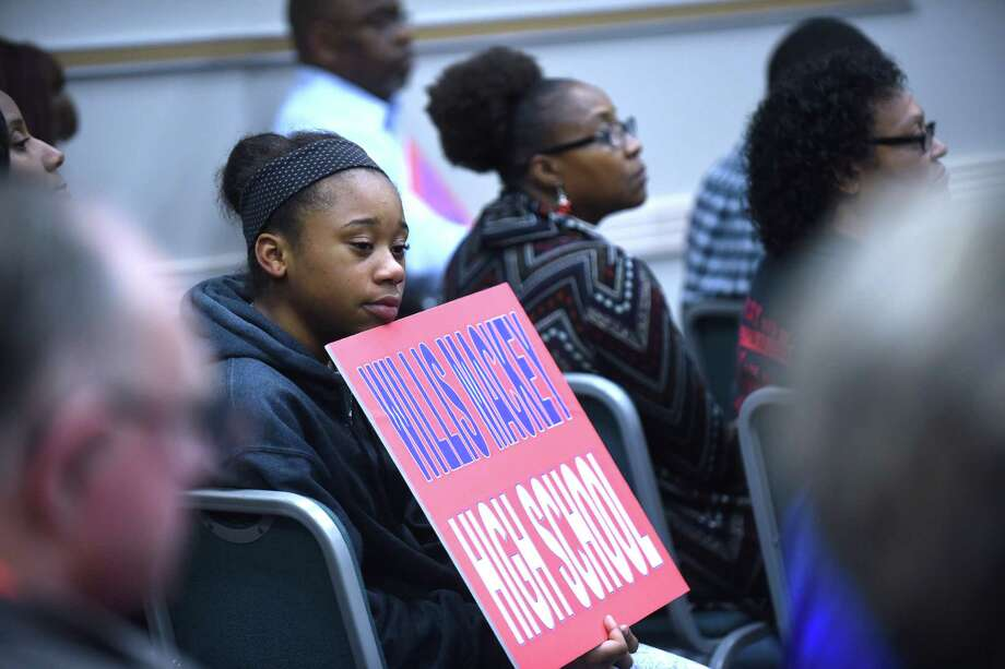 A young woman holds a sign supporting Willis Mackey during a special meeting called by the Judson ISD's board of trustees on Wednesday, Dec. 9, 2015. The board and the public discussed rescinding the naming of the district's new high school after former superintendent Willis Mackey, who took a buyout and is still on the district's payroll. Photo: Billy Calzada, Staff / San Antonio Express-News / San Antonio Express-News