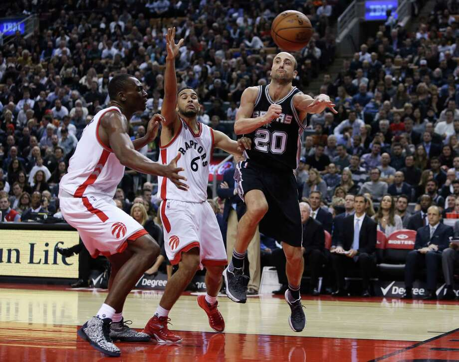 TORONTO, ON - DECEMBER 09:  Manu Ginobili #20 of the San Antonio Spurs passes the ball as Bismack Biyombo #8 and Cory Joseph #6 of the Toronto Raptors defend during an NBA game at the Air Canada Centre on December 09, 2015 in Toronto, Ontario, Canada.  NOTE TO USER: User expressly acknowledges and agrees that, by downloading and or using this photograph, User is consenting to the terms and conditions of the Getty Images License Agreement. Photo: Vaughn Ridley, Getty Images / 2015 Getty Images
