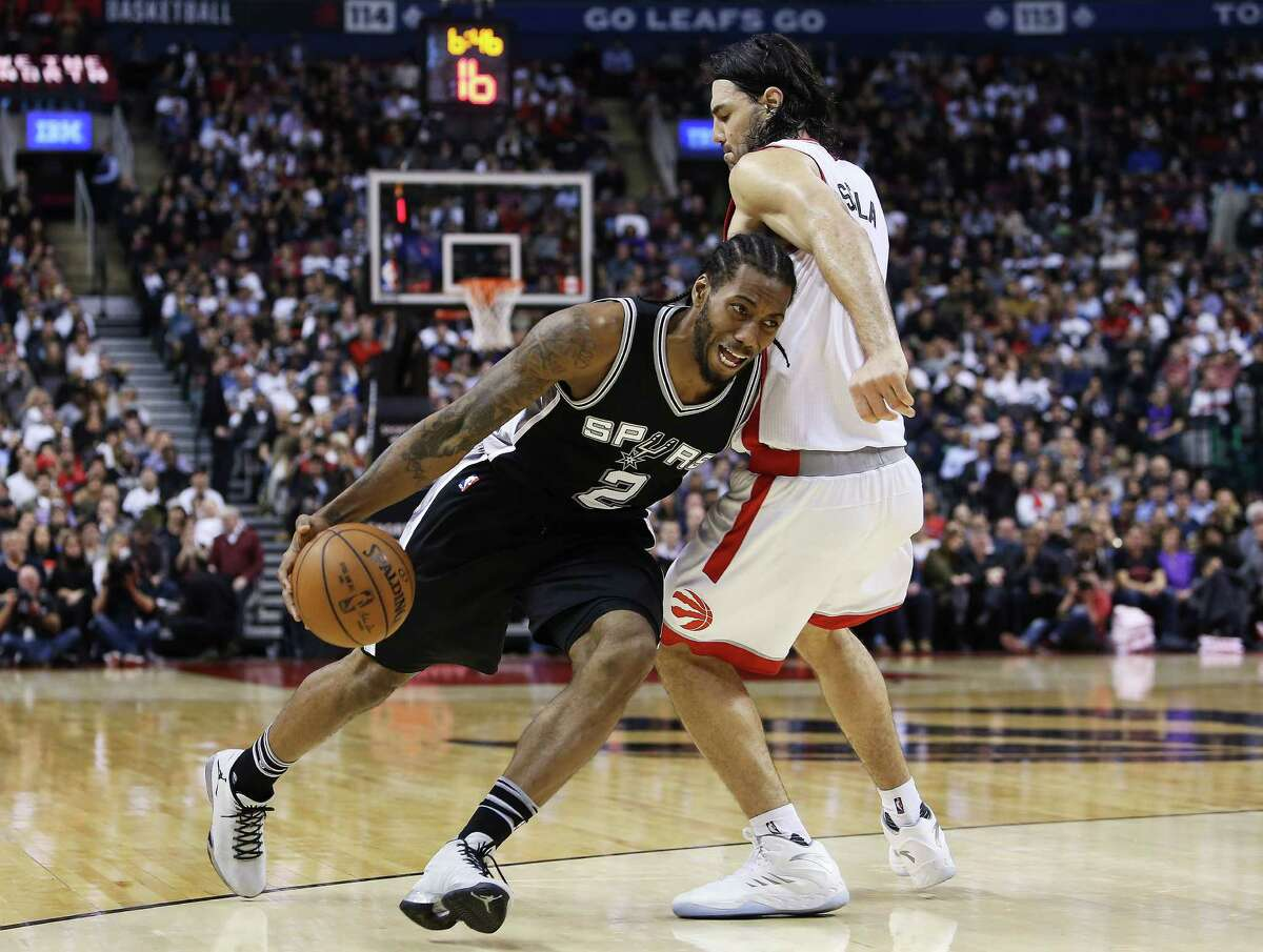 TORONTO, ON - DECEMBER 09: Kawhi Leonard #2 of the San Antonio Spurs dribbles around Luis Scola #4 of the Toronto Raptors during an NBA game at the Air Canada Centre on December 09, 2015 in Toronto, Ontario, Canada. NOTE TO USER: User expressly acknowledges and agrees that, by downloading and or using this photograph, User is consenting to the terms and conditions of the Getty Images License Agreement.