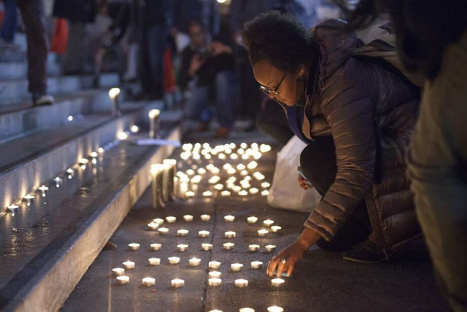 Brittany Moore, a Black Lives Matter member, lights candles outside San Francisco City Hall, Wednesday, Dec. 9, 2015, in San Francisco, Calif. The S.F. Police Commission met inside City Hall and talked about the possibility of equipping police officers with Tasers following the fatal shooting of Mario Woods. It's a proposal that was turned down twice by the commission in recent years. Woods' case has brought the proposal back. Woods was shot and killed by police officers after police say Woods was armed with a knife and walked toward officers. Photo: Santiago Mejia, Special To The Chronicle