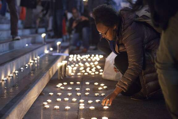Brittany Moore, a Black Lives Matter member, lights candles outside San Francisco City Hall, Wednesday, Dec. 9, 2015, in San Francisco, Calif. The S.F. Police Commission met inside City Hall and talked about the possibility of equipping police officers with Tasers following the fatal shooting of Mario Woods. It's a proposal that was turned down twice by the commission in recent years. Woods' case has brought the proposal back. Woods was shot and killed by police officers after police say Woods was armed with a knife and walked toward officers.