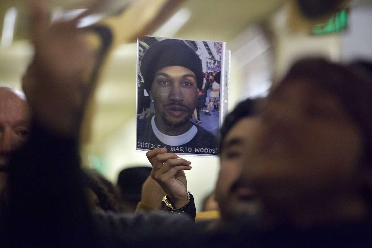 A woman holds a photo of Mario Woods at San Francisco City Hall, Wednesday, Dec. 9, 2015, in San Francisco, Calif. The S.F. Police Commission met inside City Hall and talked about the possibility of equipping police officers with Tasers following the fatal shooting of Mario Woods. It's a proposal that was turned down twice by the commission in recent years. Woods' case has brought the proposal back. Woods was shot and killed by police officers after police say Woods was armed with a knife and walked toward officers.
