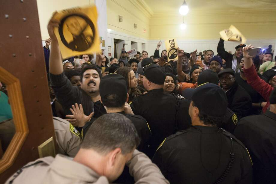 Dozens try to push into the public meeting at San Francisco City Hall, Wednesday, Dec. 9, 2015, in San Francisco, Calif. The S.F. Police Commission met inside City Hall and talked about the possibility of equipping police officers with Tasers following the fatal shooting of Mario Woods. It's a proposal that was turned down twice by the commission in recent years. Woods' case has brought the proposal back. Woods was shot and killed by police officers after police say Woods was armed with a knife and walked toward officers. Photo: Santiago Mejia, Special To The Chronicle