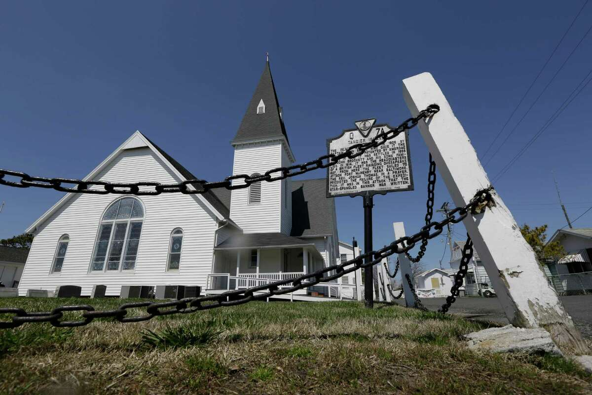 FILE - This Wednesday April 3, 2013 file photo shows a chain fence that surrounds the Swain Memorial Church on Tangier Island, Va. The island and portions of the Virginia coast along Chesapeake Bay are especially vulnerable to climate change because of glaciers thousands of years ago that gouged out the 200-mile bay and a meteor a meteor that slammed into the lower bay 35 million years ago like an exclamation point.