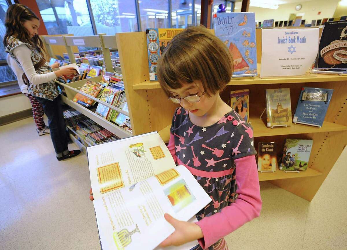 File photo: Alison Powell, 7, of Albany finds a book she likes in the new Jewish Book section at the John Bach library on Friday, Dec. 9, 2011 in Albany, N.Y. (Lori Van Buren / Times Union)