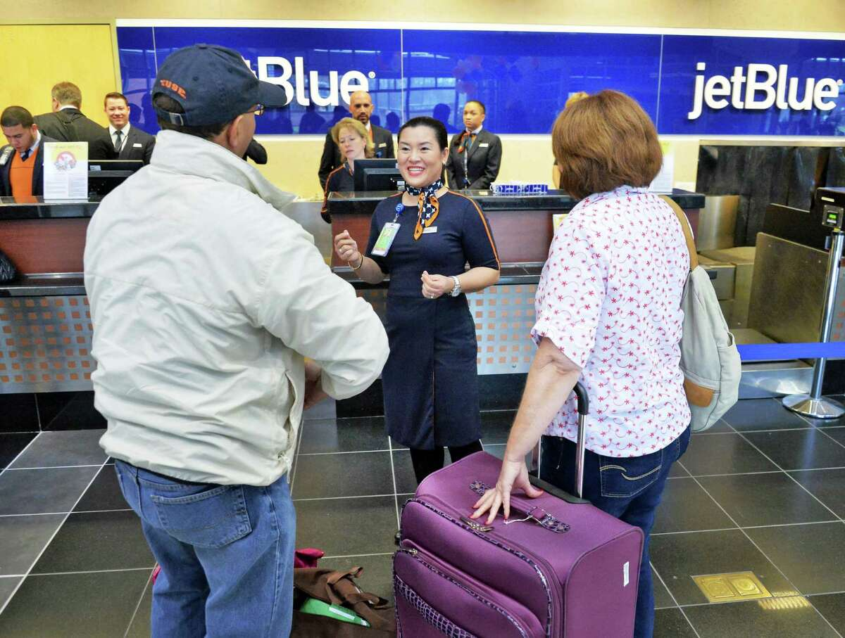 JetBlue airport operations crew member Glenda Hernaez, center, welcomes passengers to their ticket counter at Albany International Airport Thursday Dec. 10, 2015 in Colonie, NY. (John Carl D'Annibale / Times Union)