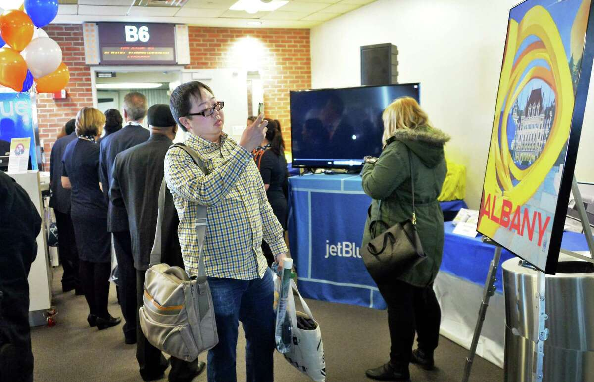 Adrian Leung of Los Angeles takes a photo of an Albany poster as he arrives with the first JetBlue passengers to arrive at Albany International Airport Thursday Dec. 10, 2015 in Colonie, NY. (John Carl D'Annibale / Times Union)