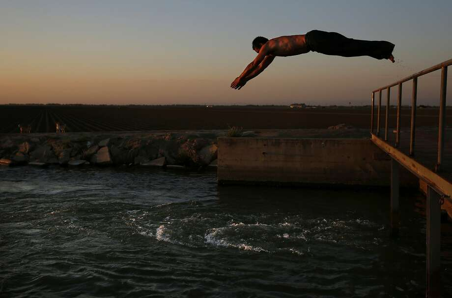 Martín Hernandez Mena, 50, dives into an irrigation canal in June near the shantytown he lives in located in a dried up canal bed on Westlands Water District land outside of Mendota, Calif. Photo: Leah Millis, The Chronicle