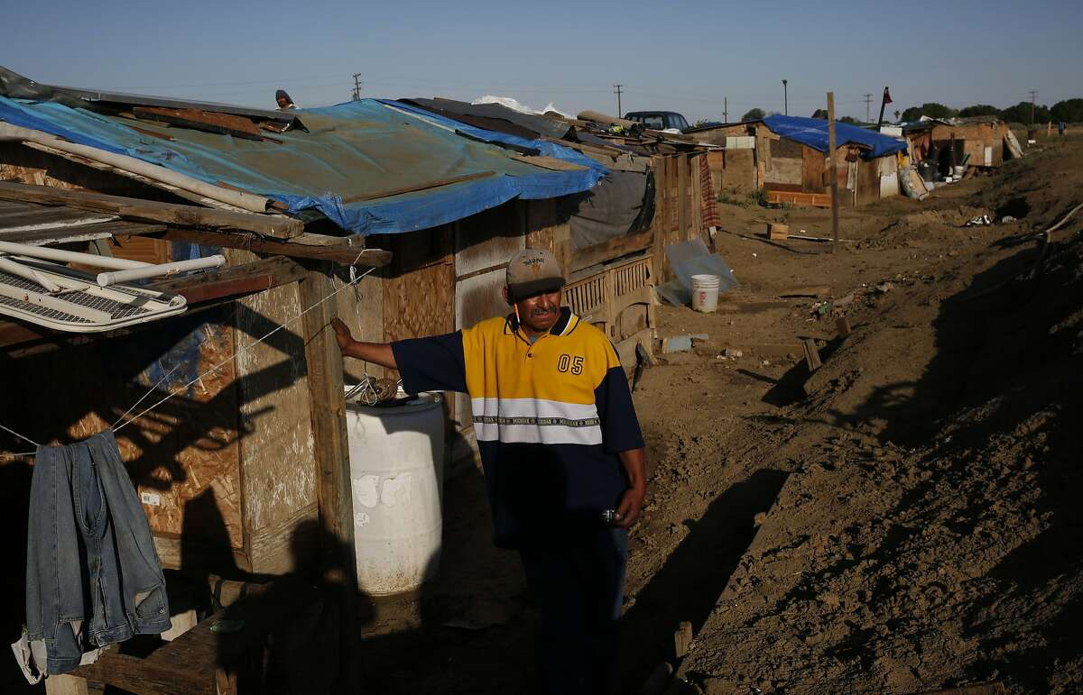 Martín Hernandez Mena, 50, leans against a home he built himself in a shantytown in a dried up canal bed on Westlands Water District land on the outskirts of Mendota, Calif.