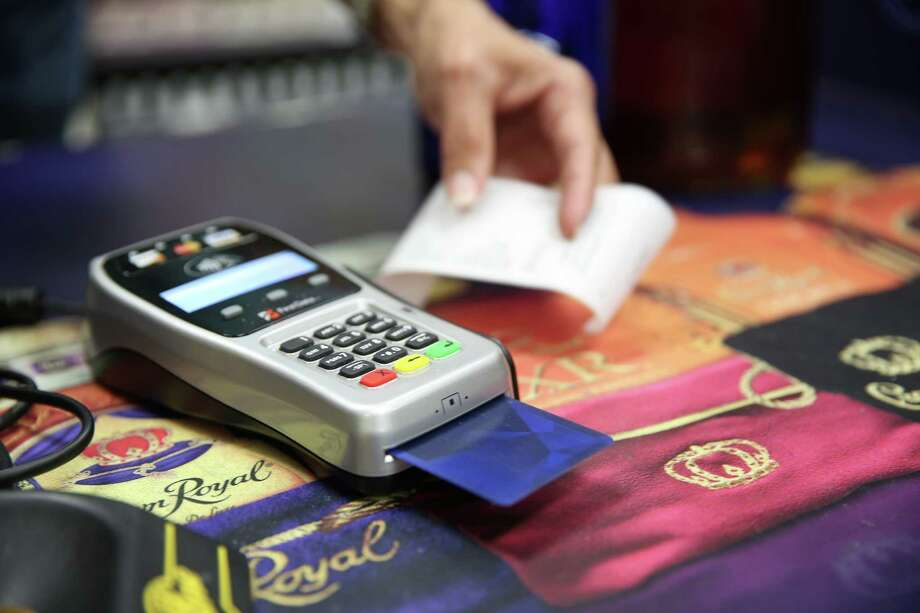 A customer uses a chip credit card at ISW Champions wine and spirits store. Photo: Elizabeth Conley, Staff / © 2015 Houston Chronicle