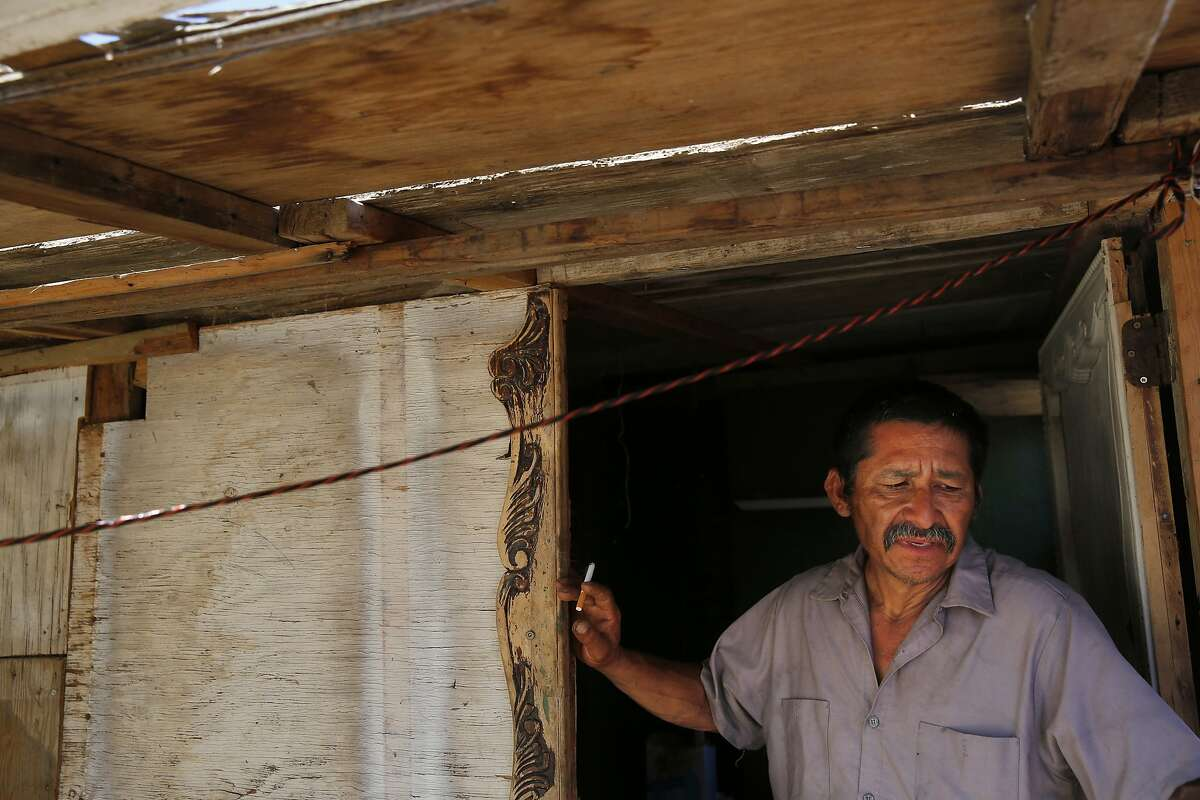Martín Hernandez Mena , 50, smokes a cigarette while standing in the doorway of the home he built in a shantytown situated in a dried up canal bed on Westlands Water District land outside of Mendota, Calif.