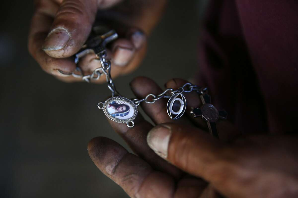 Martín Hernandez Mena, 50, palms a keychain he carries around with him featuring the Virgin Mary and crosses while sheltering from the sweltering heat in his home in the shantytown situated in a dried up canal bed on Westlands Water District land outside of Mendota, Calif.