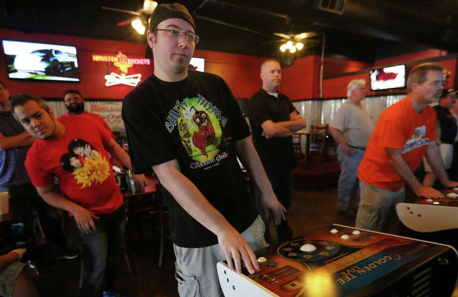 Players look over the should of Mark Stenmark, who is ranked No. 1 in the world in Golden Tee, while playing during a charity tournament on Saturday, April 18, 2015, in Houston. Golden Tee is not just a bar game for Stenmark, who makes upwards of $70,000 a year playing. ( Mayra Beltran / Houston Chronicle ) Photo: Mayra Beltran, Staff / © 2015 Houston Chronicle