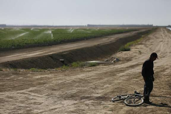 "Mart'n Hernandez Mena, 50, prepares to take off his shoes before getting into an irrigation canal to cool off from the sweltering heat June 25, 2015 near the shantytown he lives in located in a dried up canal bed on Westlands Water District land outside of Mendota, Calif. Mena has lived for a year and a half in the canal bed after he could no longer afford rent in town. Mena has lived in the U.S. for 12 years and has four grown children in Mexico, where he is from. He used to have steady farm work, starting with water melons, cantaloupes, grapes, tomatoes and pomegranate. The last few years he worked in pistachios and almonds and it was five years ago that he last had steady work as an employee. Since then, he says, it has been harder to find work. Mena mostly survives by doing work for others who live in the shantytown, such as building and fixing things for them. Sometimes he finds odd jobs in Mendota working for people in town.""I keep thinking and hoping of finding ways to get out of this canal. Once IÕm free from that, I can focus on other things.Ó Mena said in Spanish. ÒAll your energy goes to just getting by here.""   Those who live in the encampment and others from Mendota say that there have been a small number of structures in the canal bed for years. But as California entered into the third and fourth years of one of the worst droughts in its modern history, the shantytown bloomed to nearly 30 structures. Mendota has a population of about 11,500 people with more than 40 percent of the population living below the poverty line. Steady work has become more and more difficult to find for community members who depend heavily on the agriculture industry. After months of litigation, Westlands Water District evicted the shantytown residents in November."