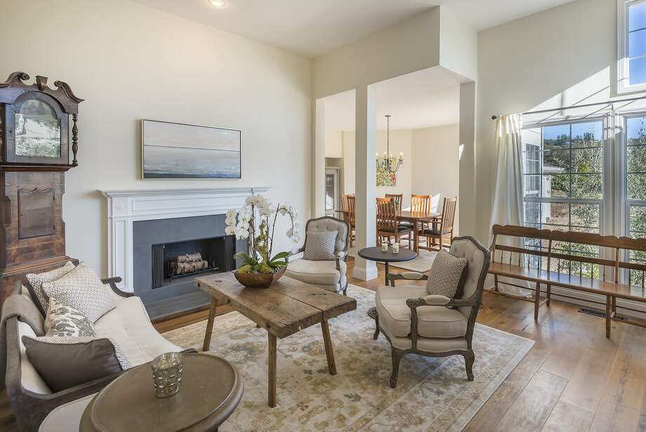 A wood-burning fireplace with stone surround accents a public room finished with wide-plank hardwood flooring. Photo: Paul Rollins Photography