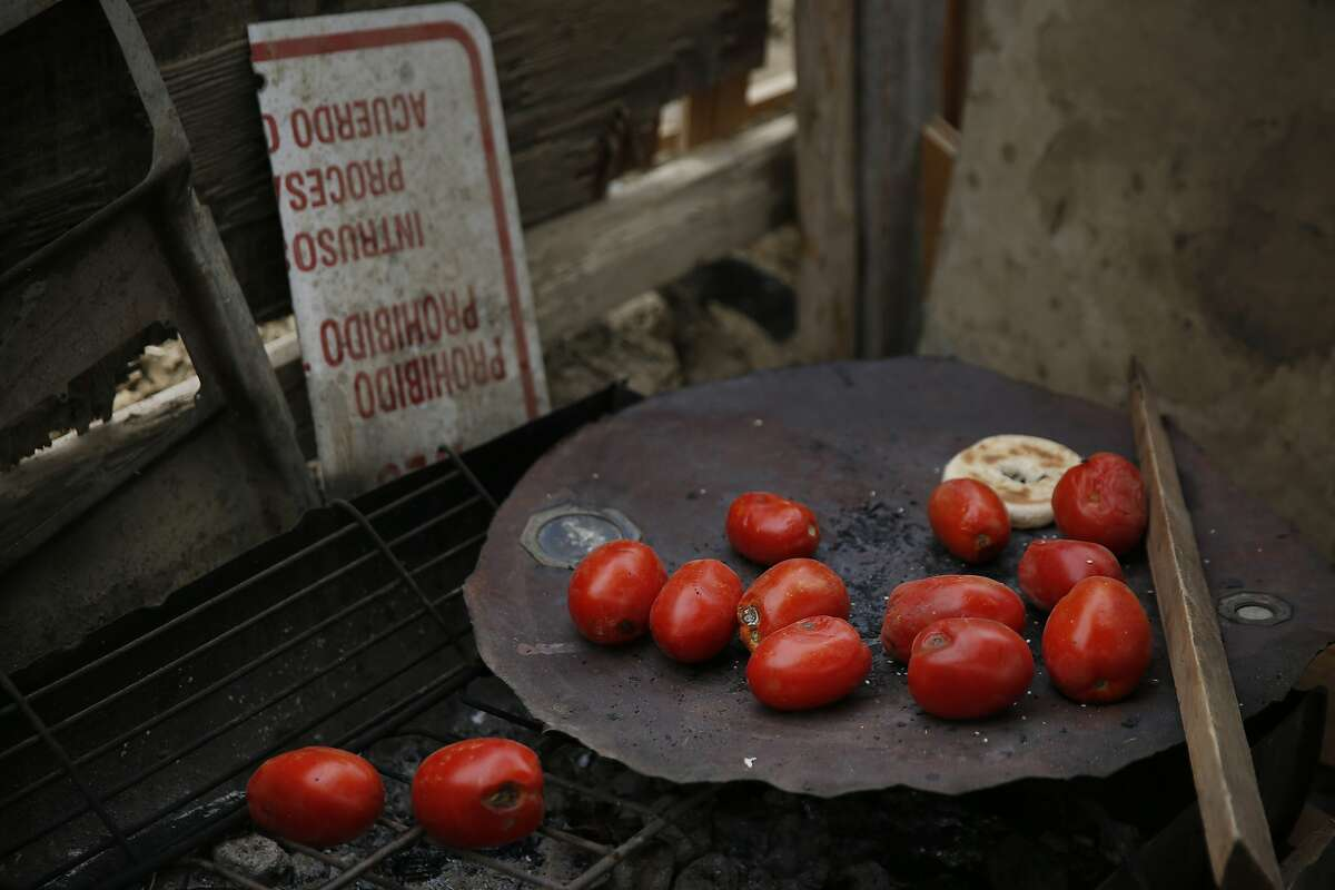A collection of donated tomatoes lay strewn about a cooking area outside of Mario Rodriguez's home in the shantytown situated in a dried up canal bed on Westlands Water District land outside of Mendota, Calif.