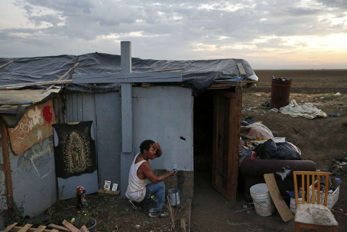 Edgar Torres Castro, 40, paints the outside of his home as evening falls in the shantytown in a dried canal bed on Westlands Water District land on the outskirts of Mendota, Calif.