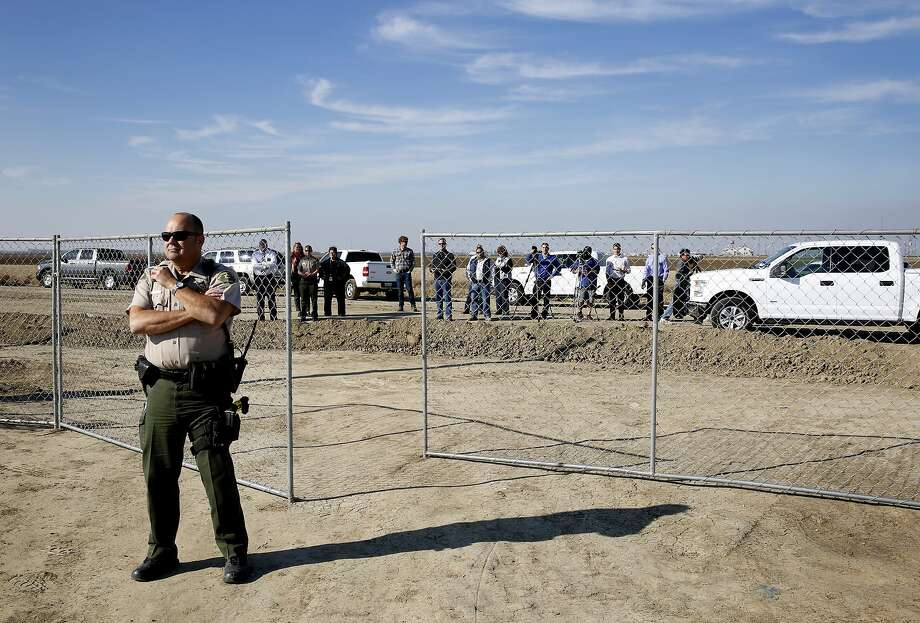 Representatives of the media, Westlands Water District and the sheriff's office wait outside of a temporary fence around the shantytown to observe as residents of the encampment are evicted. Photo: Leah Millis, The Chronicle