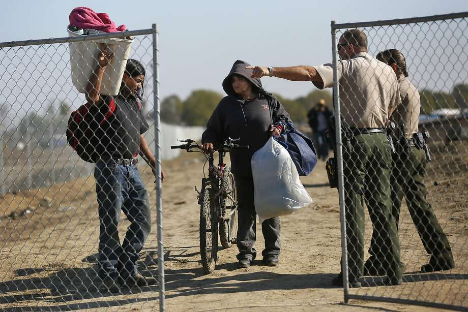"""Maricela Montejano, 49, center, a resident of the shantytown, and Gerardo """"Gerry"""" Anzorena, left, are directed out of a temporary fence surrounding the encampment as they are evicted by the Fresno County Sheriff's Office from the dried up canal bed on Westlands Water District land outside of Mendota, Calif. Photo: Leah Millis, The Chronicle"""