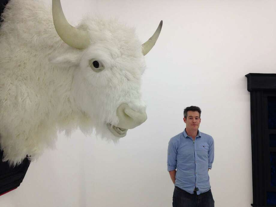 "Sculptor Pete Duggins with ""White Buffalo,"" one of the realistic pieces he has created for his solo show ""The Great White Whale,"" on view through Dec. 19 at Art Palace Gallery. Photo: Molly Glentzer"