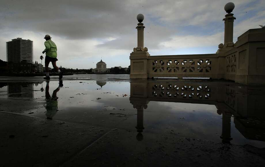 A jogger circles Lake Merritt following a morning rain storm in Oakland, Calif., on Thursday December 10, 2015, during a break between storms with more rain expected later today. Photo: Michael Macor, The Chronicle