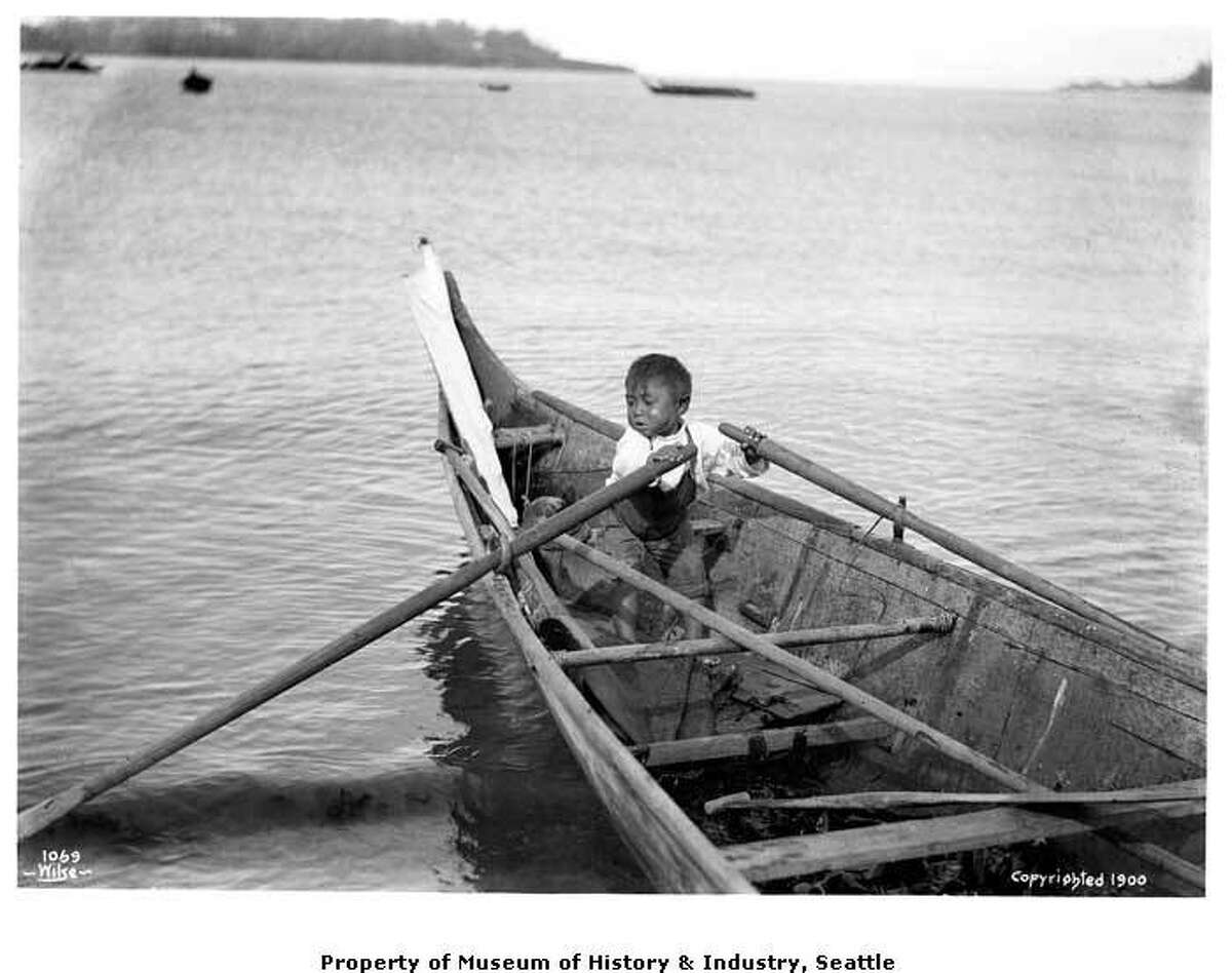 """""""Norwegian photographer Anders Wilse took a number of photographs of the Makah people at Neah Bay, on Washington's Olympic Peninsula. In this photo, taken around 1900, a small boy handles the oars of a large cedar canoe at Neah Bay. Makah children learned how to handle canoes at a young age."""" -MOHAI. Photo courtesy MOHAI, Anders Beer Wilse Photographs collection, image number 1988.33.136."""