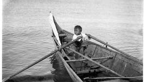 """Norwegian photographer Anders Wilse took a number of photographs of the Makah people at Neah Bay, on Washington's Olympic Peninsula. In this photo, taken around 1900, a small boy handles the oars of a large cedar canoe at Neah Bay. Makah children learned how to handle canoes at a young age."" -MOHAI. Photo courtesy MOHAI, Anders Beer Wilse Photographs collection, image number 1988.33.136."