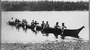 """In 1909, Jack Adams, a member of the Suquamish Tribe, built a canoe for an Indian canoe race at Seattle's Alaska-Yukon-Pacific Exposition. The event was on September 6, and the finish line was at the foot of the fair's Pay Streak, in Portage Bay. Adams built the 48-foot craft from a single cedar log. In this photo, he and ten other men paddle the canoe on Portage Bay."" -MOHAI. Photo courtesy MOHAI, Seattle Historical Society Collection, image number shs11726."