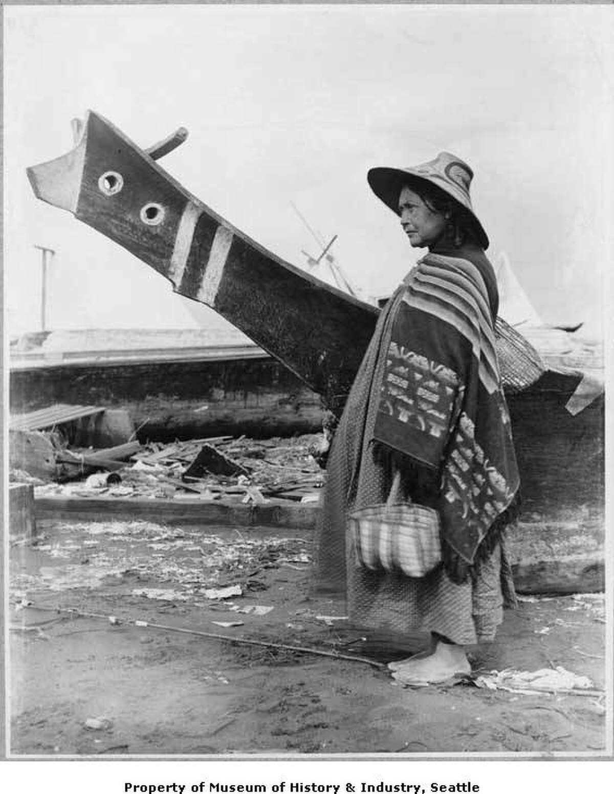 """""""Native people from many parts of the Northwest Coast came to Seattle to trade and buy supplies. In this 1898 photo by O.P. Anderson, a Native American woman stands by a canoe at the Seattle waterfront. The tall prow of the canoe and the design of her hat suggest that she is from Vancouver Island or some other part of coastal Canada. The photo was taken two blocks south of King Street, near First Avenue."""" -MOHAI. Photo courtesy MOHAI, Seattle Historical Society Collection, image number shs321."""