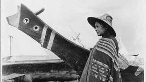 """Native people from many parts of the Northwest Coast came to Seattle to trade and buy supplies. In this 1898 photo by O.P. Anderson, a Native American woman stands by a canoe at the Seattle waterfront. The tall prow of the canoe and the design of her hat suggest that she is from Vancouver Island or some other part of coastal Canada. The photo was taken two blocks south of King Street, near First Avenue."" -MOHAI. Photo courtesy MOHAI, Seattle Historical Society Collection, image number shs321."