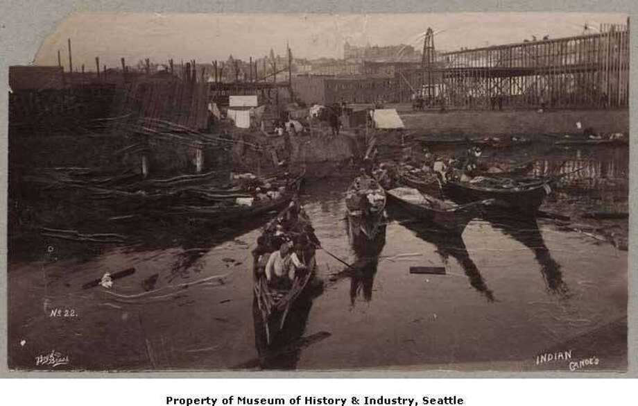 """Native Americans in Seattle """"By the late 19th century, most Native Americans in the Seattle area had been moved to reservations. Many of these people made regular visits to Seattle to sell shellfish and souvenirs, or to look for odd jobs in the city. Each fall, many traveled through Seattle on their way to and from harvesting hops. They usually camped at Ballast Island or elsewhere along the waterfront. In this photo, a number of Native American canoes line the Seattle waterfront south of Yesler Street. It was taken sometime between 1890 and 1893 by the Seattle firm of Boyd & Braas."""" -MOHAI Photo: Courtesy MOHAI"""