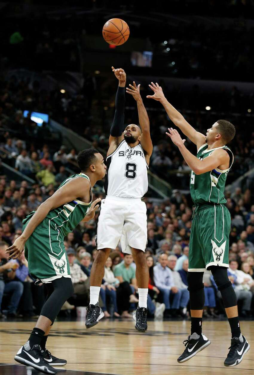 Spurs' Patty Mills (08) attempts a shot against the Milwaukee Bucks' John Henson (left) and Michael Carter-Williams (05) at the AT&T Center on Wednesday, Dec. 2, 2015. Spurs defeated the Bucks, 95-70. (Kin Man Hui/San Antonio Express-News)