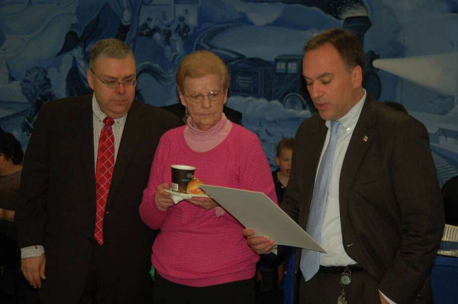 From left, Republican Registrar of Voters Fred DeCaro III and Democratic Registrar Sharon Vecchiolla listen as First Selectman Peter Tesei reads a proclamation honoring poll workers for their volunteer efforts. Photo: / Ken Borsuk