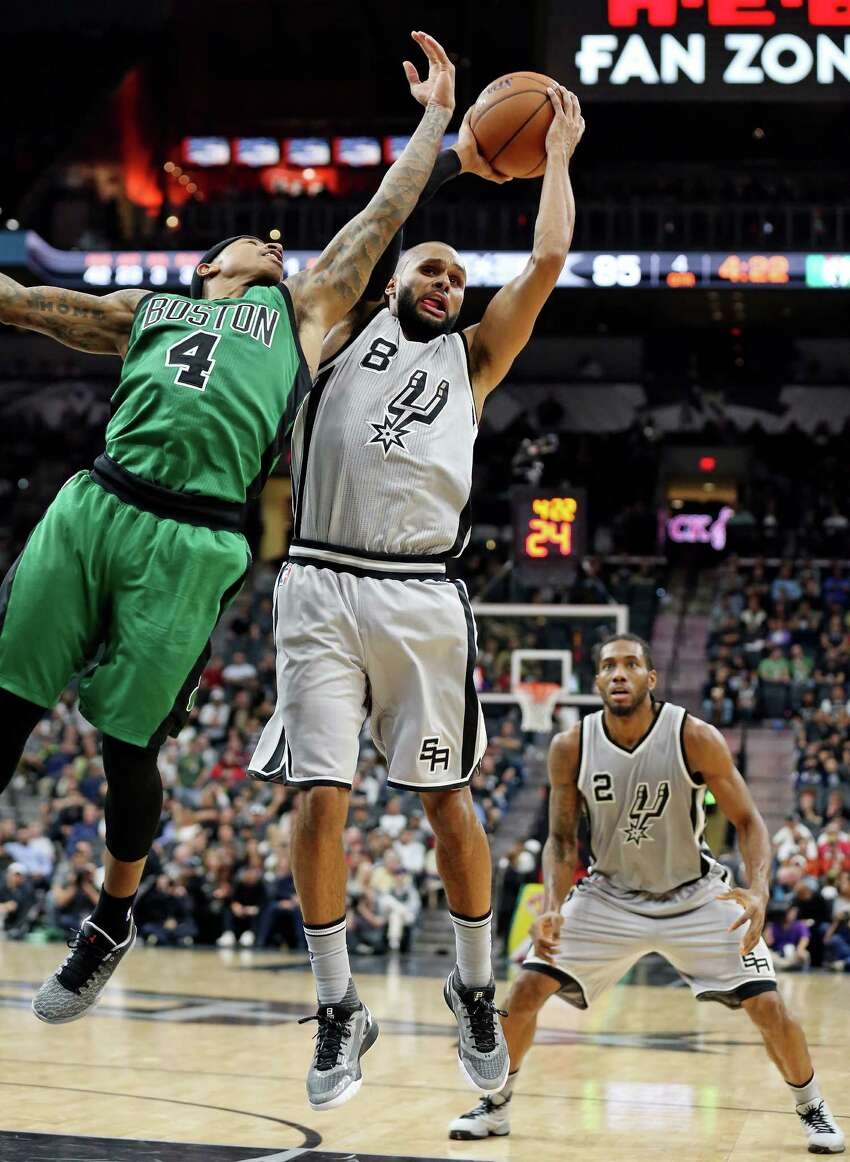 San Antonio Spurs' Patty Mills and Boston Celtics' Isaiah Thomas grab for a rebound during second half action as San Antonio Spurs' Kawhi Leonard looks on Saturday Dec. 5, 2015 at the AT&T Center. The Spurs won 108-105.
