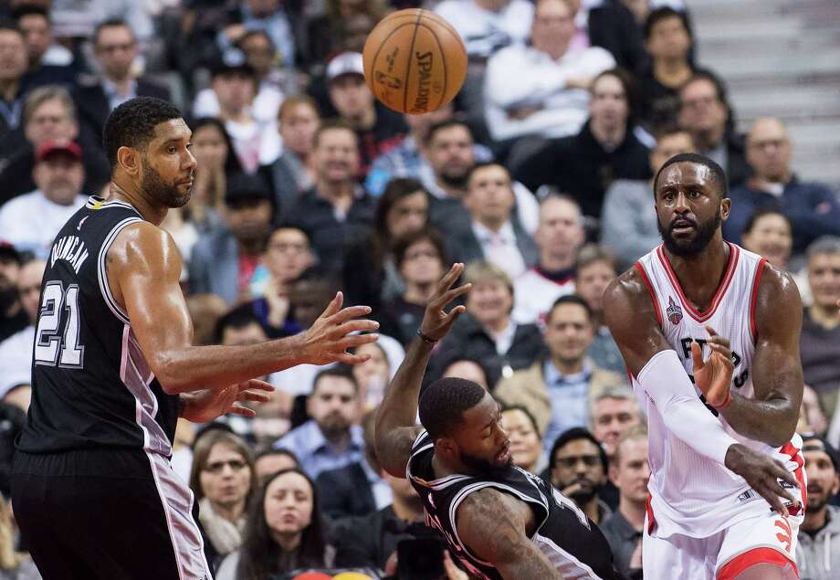Raptors forward Patrick Patterson, right, knocks over San Spurs' guard Jonathon Simmons, center, as his teammate, Tim Duncan (21), looks on during first half in Toronto on Dec. 9, 2015. Photo: Nathan Denette /Associated Press / The Canadian Press