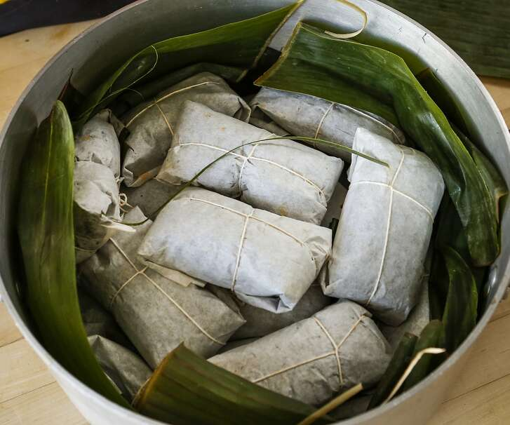 Fanny Andrade surrounds nacatamales in a pot with banana leaves on Thursday, Dec. 10, 2015 in San Francisco, Calif.