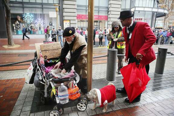 Wayne Alexis (right), Union Square ambassador, talks with Jack Hill  (left), who is homeless, at the corner of Powell and Market Streets  at the cable car turnaround as Hill prepares to put his dog  Clover Nicole (center) into a stroller on Wednesday, December 9,  2015 in San Francisco, Calif.
