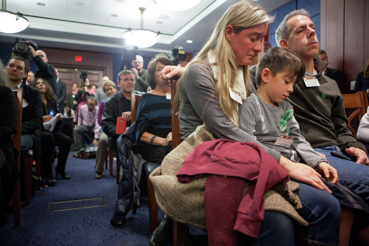 Second-grader Rafe D'Agostino, 7, sits between his parents, Noelle and Paul D'Agostino, of Newtown, on Thursday during a press conference on Capitol Hill. The family came to Washington for a vigil marking the three-year anniversary of the shooting at Sandy Hook Elementary.
