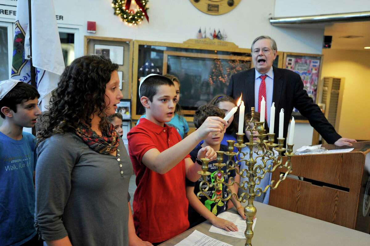 Jeremy Young, 11, lights a candle on the menorah during the annual lighting in the Government Center lobby while Stamford mayor David Martin joins the other participants in song.