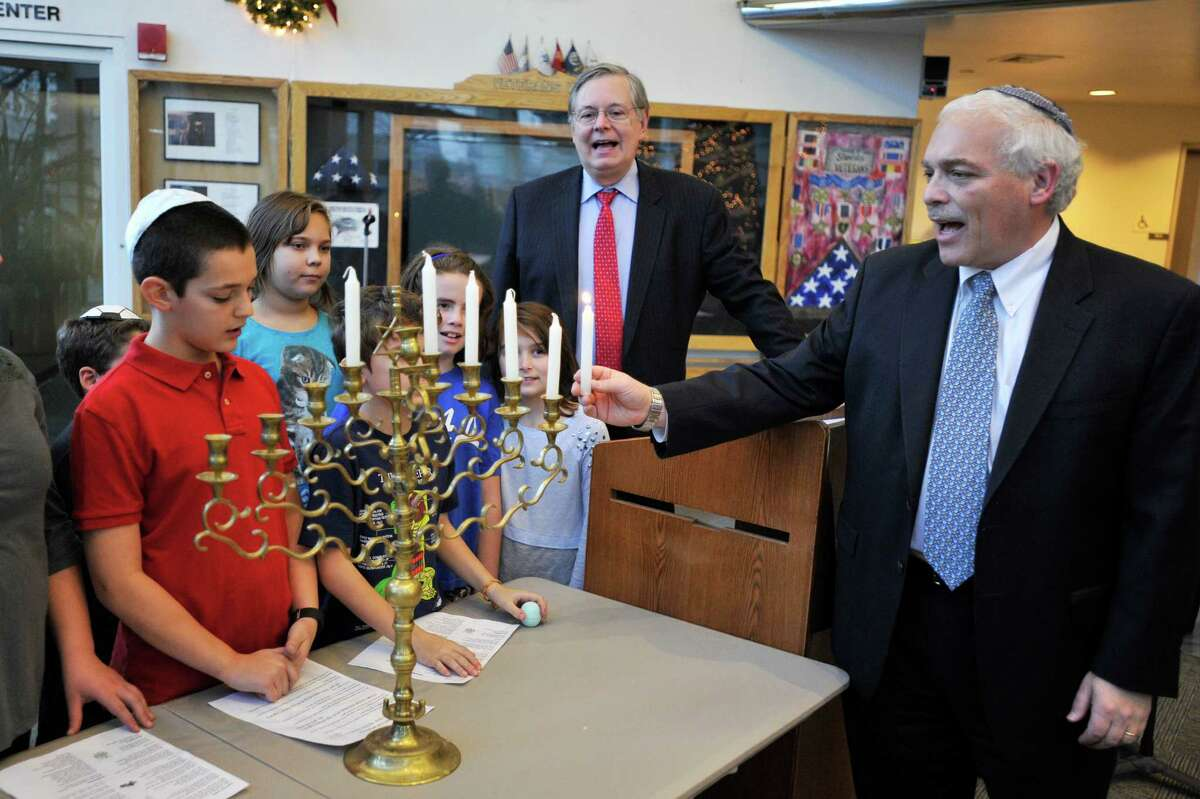 Rabbi Joshua Hammerman, of Temple Beth El, kicks off the lighting of the menorah inside the Government Center lobby with mayor David Martin and local children participating in ceremonial song.