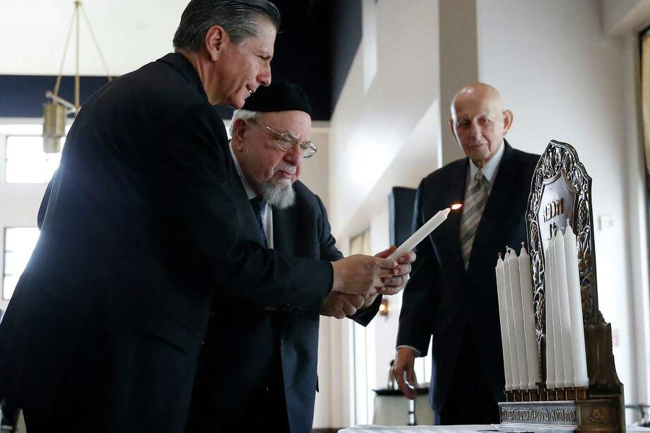 """Archbishop Gustavo Garcia-Siller (left) and Rabbi Aryeh Scheinberg join to light a candle on the Menorah during the interfaith celebration, """"Celebrating the 50th Anniversary of Nostra Aetate"""" on Thursday, Dec. 10, 2015. Rabbi Emeritus Samuel Stahl (right) of Temple Beth-El provided remarks at the celebration. (Kin Man Hui/San Antonio Express-News) Photo: Photos By Kin Man Hui / San Antonio Express-News / ©2015 San Antonio Express-News"""