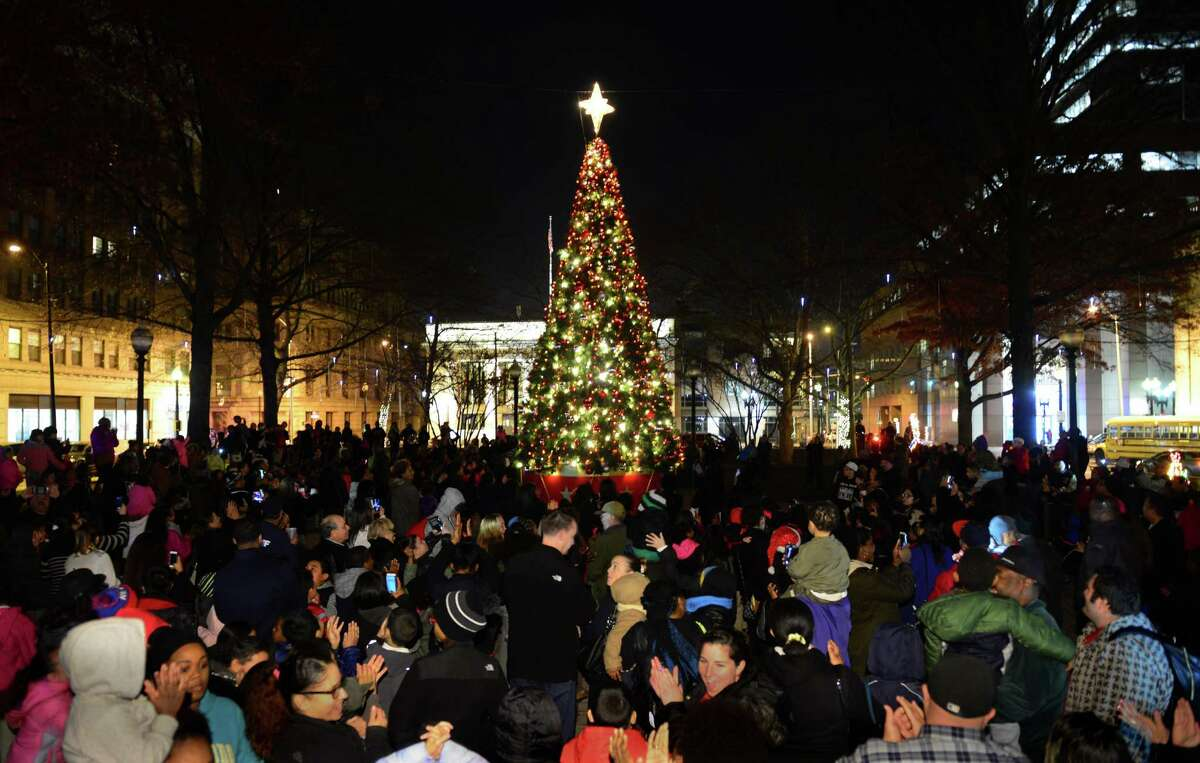 The Christmas tree on McLevy Green is lit as hundreds of residents watch in downtown Bridgeport, Conn. on Thursday Dec. 10, 2015. Mayor Joe Ganim switched on the tree with help from Santa and one of his elves. Afterwards, Santa posed for photo with youngsters.