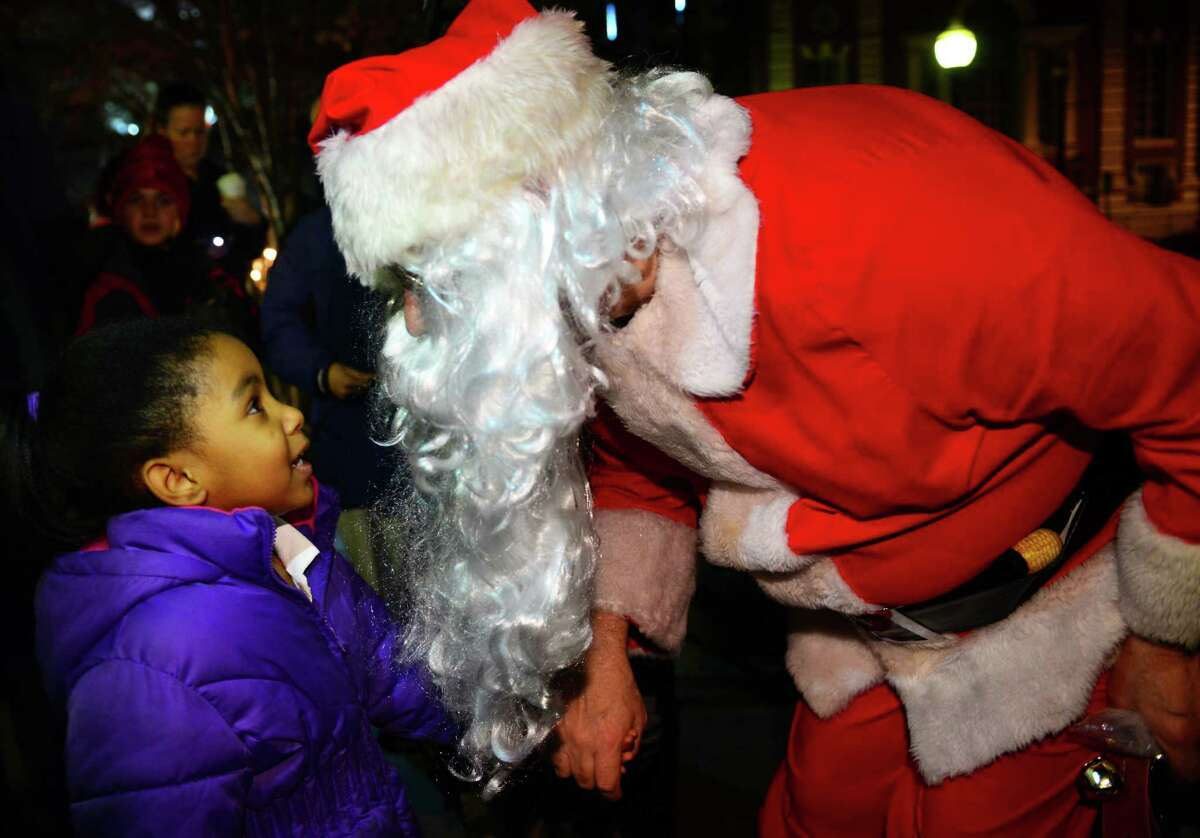 Santa leans in close as Ayanna Martin, 5, of Bridgeport, tells him want she wants for Christmas after the Christmas tree was lit on McLevy Green in downtown Bridgeport, Conn. on Thursday Dec. 10, 2015. Mayor Joe Ganim switched on the tree with help from Santa and one of his elves. Afterwards, Santa posed for photo with youngsters.