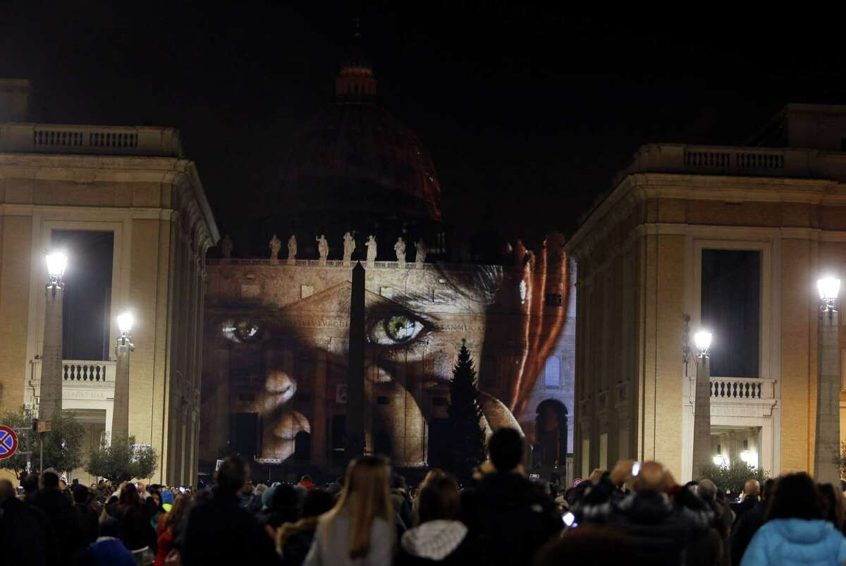 People gather to watch images projected on the facade of St. Peter's Basilica, at the Vatican, Tuesday, Dec. 8, 2015. The Vatican is lending itself to environmentalism with a special public art installation timed to coincide with the final stretch of climate negotiations in Paris. On Tuesday night, the facade of St. Peter's Basilica has been turned into a massive backdrop for a photo light show about nature organized by several humanitarian organizations. Organizers offered the installation as a gift to Francis to mark his Holy Year of Mercy, which began Tuesday.